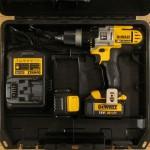 La machine DeWALT DCD985L2, 2 batteries 3.0 Ah, le chargeur multi-tensions et la poignée auxiliaire.