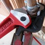 Gros plan sur le serrage d'un raccord 3 pièces avec la clé serre-tube